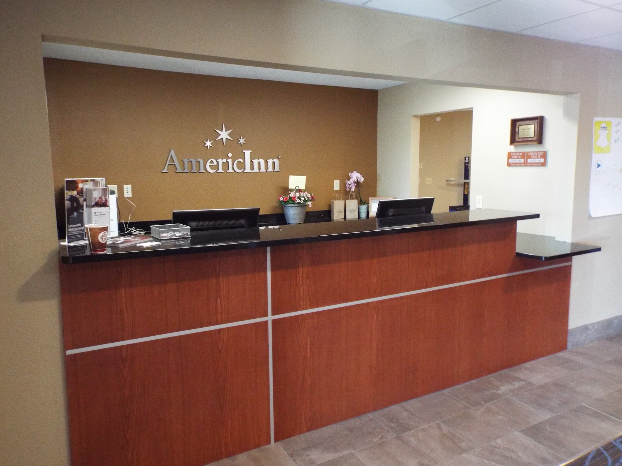 Updated Lobby and reception area of AmericInn that boasts custom architectural millwork and molding by Dras Cases.